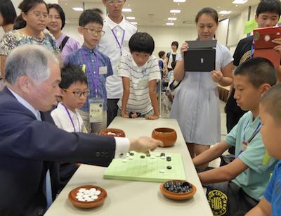 Otake Hideo and three kids playing pair go
